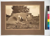 House at Summer Pueblo of Acometa, New Mexico. Mother and daughter baking bread in oven introduced...