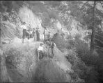 Asian construction workers widening a toll road below the Pasadena Gap, San Gabriel Mountains.