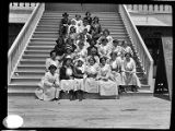A group portrait of a group of young women sitting on the steps at the Balboa Pavilion.