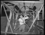 Man working on airplane frame.