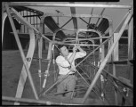 Man working on airplane frame with 2 variants of man with single engine airplane.