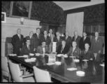 Jack Horton with 4 other executives seated at conference table and 10 additional executives...