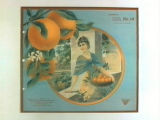Stock label: woman on balcony holding basket of oranges overlooking groves.