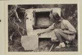 "Shirley Morse Marston.  Examining the stern section of the ""Lota-ve"" at the foot of..."